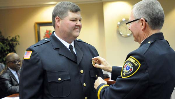 Longtime Greenville Fire Department Chief Mike Phillips pins a badge on newly appointed Chief Chad Phillips. (Advocate Staff/Andy Brown)