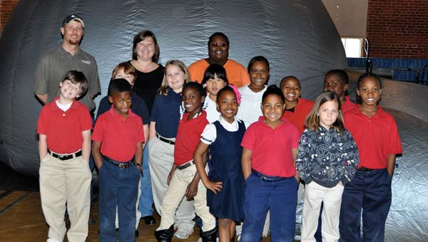 Woodmen of the World's Jason Whittle and W.O. Parmer Elementary School teacher Staci Watson and substitute teacher Jessica Benjamin pose with second graders from W.O. Parmer Elementary after the students were treated to a traveling planetarium on Friday. (Advocate Staff/Fred Guarino)