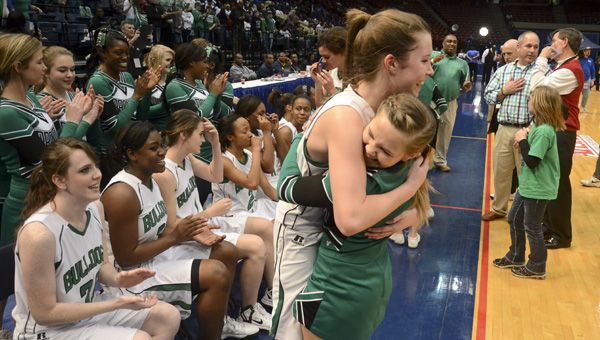 Peyton Hill hugs a cheerleader in celebration.