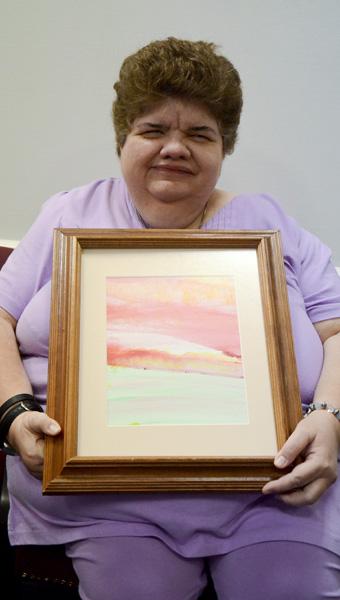 Debbie Warren holds up a framed piece of her watercolor art.