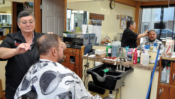 Linda Stuckey, owner of Stuckey's Barber & Style Shop, gives regular customer John Smith a trim. Stuckey began cutting hair at the barbershop in 1992. She purchased the business in 2005 from longtime barber Al Middleton. (Advocate Staff/Fred Guarino)