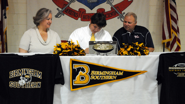 """Fort Dale Academy senior Davis Crocker signed a national letter of intent on Monday to play football for Birmingham-Southern College. Pictured are, from left to right, Donna-Marie Crocker, Davis Crocker, and Fort Dale head coach James """"Speed"""" Sampley. (Advocate Staff/Andy Brown)"""