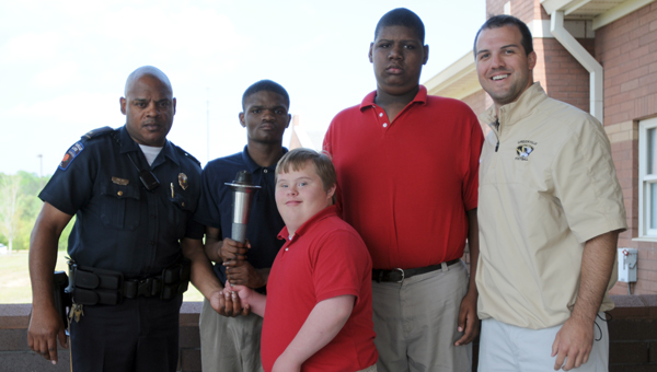 Lt. Malcom Owens presents the official Special Olympics torch to special education students at Greenville High School on Tuesday. The second annual Butler County Special Olympics is scheduled for April 26 at Tiger Stadium in Greenville, and will include students from throughout the Butler County School district. The torch was delievered to GHS by the Foley Police Department. The torch will be delivered to the stadium by the Greenville Police Department's SRT team to open the games. The team will carry the torch from the police station through downtown to the stadium. The games will start at 8:30 a.m. Pictured with Owens are, from left to right, Jaylon Hamilton, Matthew Davis, Diontae Pugh and Richard Kelly. (Advocate Staff/Andy Brown)