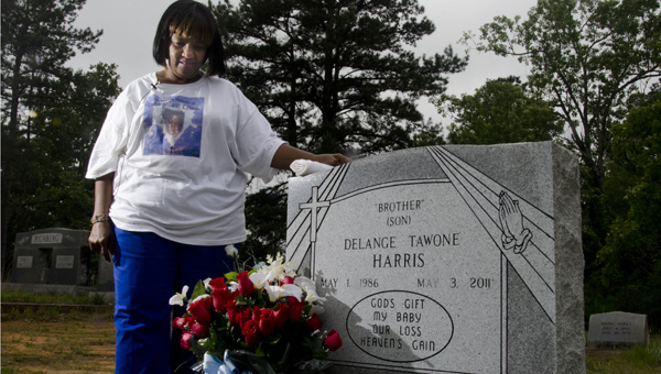 Dora Harris stands beside the grave of her son, DeLange Harris, whose murder still remains unsolved.