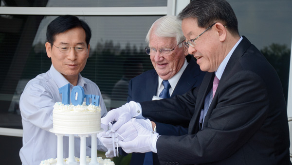 Director of Hyundai Motor Manufacturing Alabama K. Y. Lee, Luverne mayor Joe Rex Sport and owner and CEO of Shin Young Metals Ho Gap Kang work together to cut a 10th birthday cake for SMART at last Saturday's ceremony.