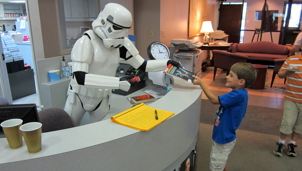A Stormtrooper with the Alabama 501st Legion helps Tad Smith checkout his book at the Greenville-Butler County Public Library's Star Wars Day in 2012. (Courtesy Photo)