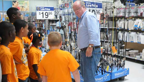 Mayor Dexter McLendon helps the Dunbar campers pick out fishing rods for Wednesday's fishing expedition.