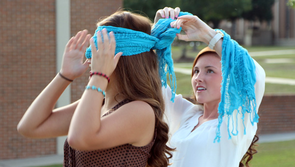 Amy Lewis of Greenville, right, assists Courtney Fussell of Straughn in the placement of a blindfold. (Submitted Photo)
