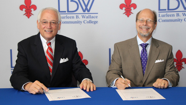 Troy University Chancellor Dr. Jack Hawkins Jr., left, and Lurleen B. Wallace Community College President Dr. Herbert Riedel sign a reverse transfer agreement between the two institutions that allows students who have transferred to Troy from LBWCC to be awarded an associate degree while working toward completing a bachelor's degree. (Courtesy Photo)
