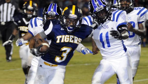 McKenzie School sophomore wide receiver Robert Shufford stiff-arms Georgiana School senior defensive back Travales Smith during the Tigers' 46-12 win Friday night. (Advocate Staff/Jonathan Bryant)