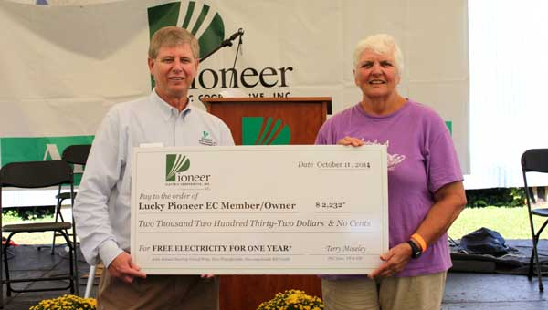 PEC general manager Terry Moseley presents the grand prize of electric credit to Mary Brown.