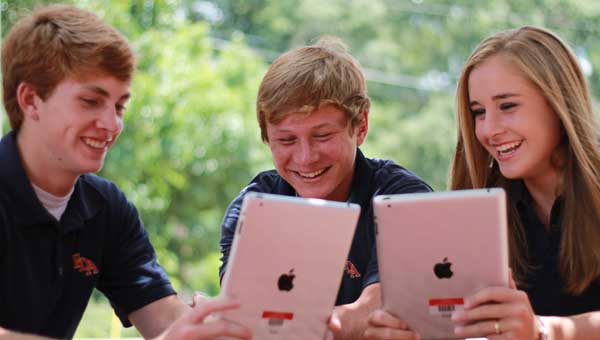 Fort Dale Academy students Stephen Hartley, Luke Taylor and Madison Ann Gaston demonstrate the proper online usage of iPads.