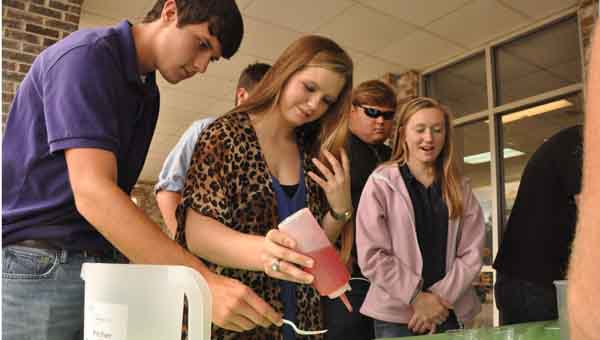 JOURNAL PHOTO | MONA MOORE From left, Goshen Agriculture Academy students Bailey Singleton and Lexi Ellisor make gummy worms as Austin Missildine and Esther Gilbert observe. The gummy worms were an experiment at Auburn University Ag Exploration Day, held in Crenshaw County's Tom Harbin Ag Center.