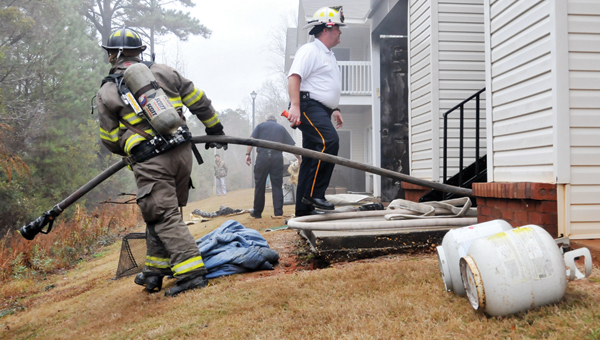 Greenville Fire Chief Chad Phillips (right) enters the apartment where a fire started on the outside patio. | ADVOCATE STAFF / ANDREW GARNER