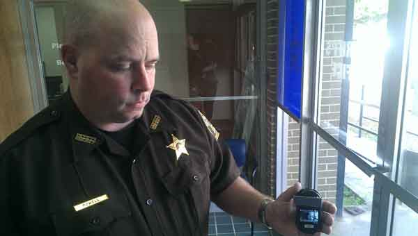 Deputy John Powell shows the size of the body camera's display. JOURNAL PHOTO | MONA MOORE