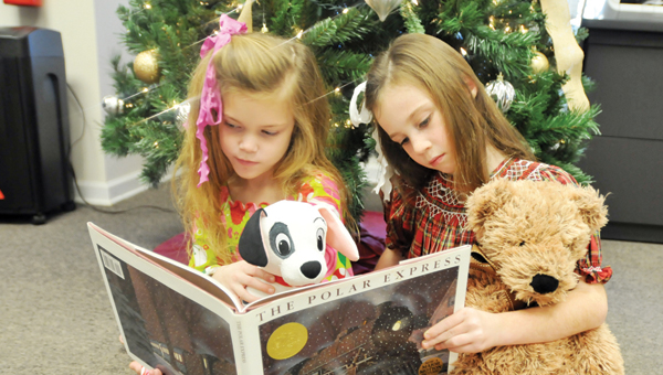 """Advocate staff / Andrew garner Bailey Lambert, 8, (left) and Caroline Meadows, 8, (right) read """"The Polar Express"""" in front of the Christmas tree. There are many different traditions people have every holiday season. 