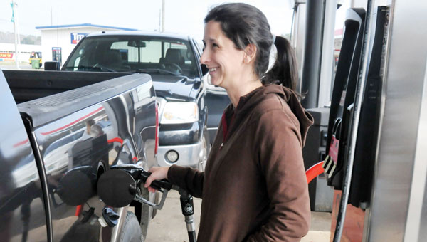 Karla McDavid of Mobile fills up her truck at the QV gas station Wednesday afternoon. Gas prices in the state have dropped significantly as of late.