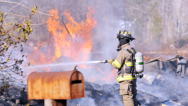 A Greenville fire fighter works to extinguish a Simpson Circle home after it caught fire from a control burn this afternoon. | Advocate Staff / Andrew Garner