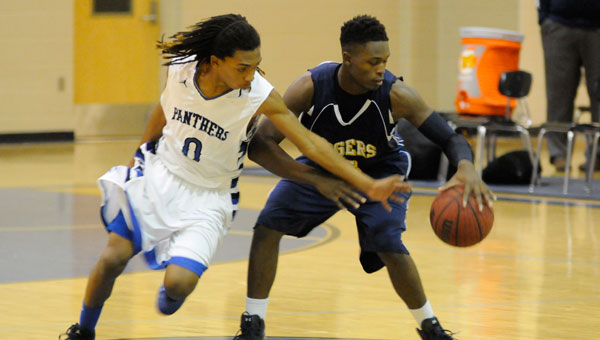 McKenzie's Terrance Clemons spins away from Georgiana defender Devin McMeans on the way to the basket.