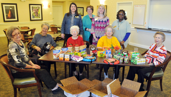 Country Place Senior Living residents and staff shown from L to R: Marion Norman, Bobbie Gamble, Mertice Porterfield, administrator Rebecca Reynolds, resident nurse Patricia Griggers, activity instructor Alaina Norman, Bobbie Terry, caregiver Katrice Bowen and Mae Poole pose for a photo Thursday afternoon after writing letters and before stuffing care packages for two Butler County soldiers. | ADVOCATE STAFF / ANDREW GARNER