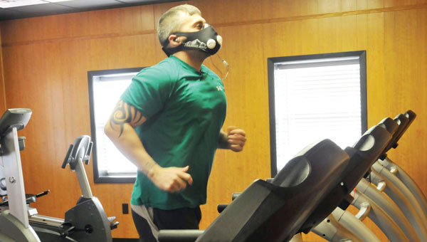 Chris Stinson runs on the treadmill Wednesday afternoon during his routine workout while wearing an elevation mask, which allows athletes to receive benefits of high-altitude training from home.