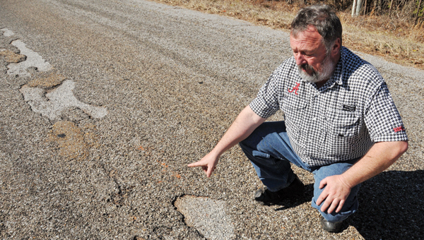 Butler County District 2 Commissioner Jesse McWilliams points to a plethora of patches on one of the county's roads that is in need of repairs. Below: A stretch of county road is shown.   ADVOCATE STAFF / ANDREW GARNER