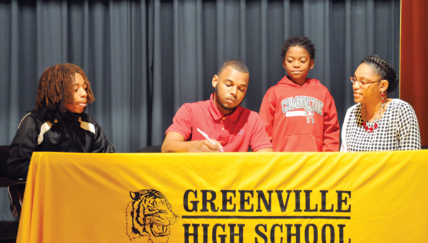 Donovan Lindo signs his letter to play football at Huntingdon College Thursday morning.  Shown with Lindo is his mother, Brandi, and brothers Brandon Posey and Keondre Thomas. | ADVOCATE STAFF / ANDREW GARNER