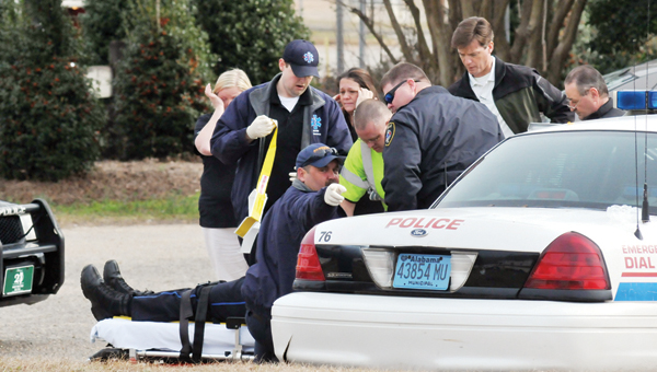 ADVOCATE STAFF PHOTOS / ANDREW GARNER Officers and emergency personnel transport Greenville Police Officer Roberto Jones to an ambulance Tuesday morning. | ADVOCATE STAFF / ANDREW GARNER