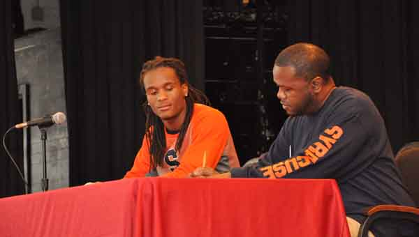Luverne quarterback Kenterius Womack (left) signed with Syracuse today. Here, he watches as his father, Kevin Womack, adds his signature to the commitment papers.