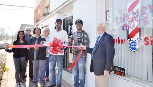 Luverne Mayor Joe R. Sport and members of the Crenshaw County Chamber of Commerce joined Rutledge resident Kentrell Jones, 20, and his family in a ribbon-cutting ceremony to mark the opening of Jones' new downtown business, Luxury Cuts Barber Shop.  JOURNAL PHOTO | MONA MOORE