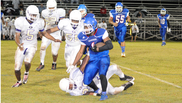 Running back Cameron Longmire stiff-arms a Goshen defender to the ground on a powerful first-down run.