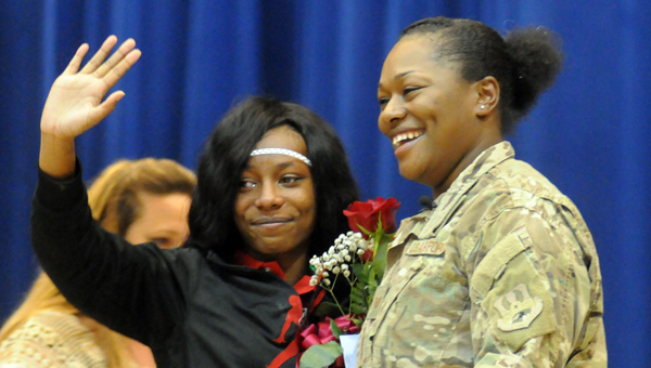 Lexis McMeans waves to the audience at the Georgaiana talent show after being surprised by her mother, U.S. Air Force Tech Sgt. Tonya Gandy, who just returned from a deployment to Afghanistan. (Advocate Staff/Andy Brown)