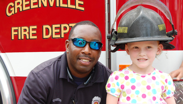 """Firefighter Holsie Griffin poses with Emma Hartin after members of the Greenville Fire Department gave children a tour of the fire engine as the Greenville-Butler County Public Library celebrated """"Hometown Heroes,"""" part of its ongoing children's Summer Reading Program. (Advocate Staff/Morgan Burkett)"""