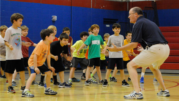 FDA head basketball coach Reggie Mantooth demonstrates a proper defensive stance to a crowd of aspiring basketball players.