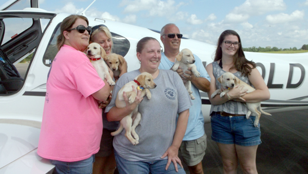 Pilots N Paws pilot Jeff Bennett, alongside four rescue volunteers from across Alabama, show off their five puppies before loading them for their trip to new loving homes in Florida as part of Pilots N Paws Sunshine Fly-Away. (Courtesy Photoo)