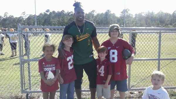 Highland Home residents (left to right, in Crimson gear) Nataleigh Myrick, Troy Kelley, Brody Kelley, Brendan Allin and Eli Vining pose with University of Alabama running back Derrick Henry. CONTRIBUTED PHOTO | KATHY VINING