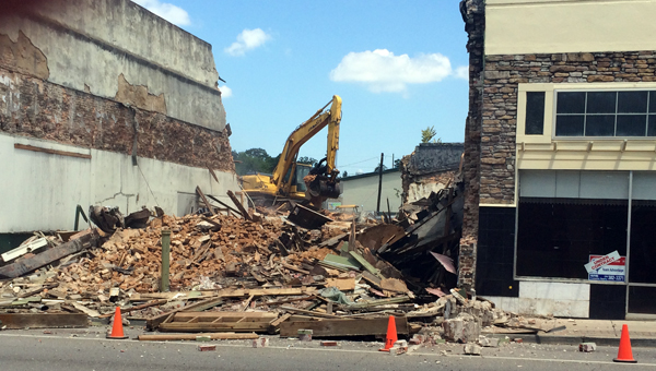 On Wednesday crews began demolishing the first of three downtown buildings purchased by the City of Greenville earlier this summer. (Advocate Staff/Andy Brown)