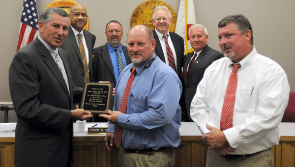 On Monday the Butler County Commission presented longtime assistant engineer John Mark Davis with a plaque honoring his nearly 21 years of service to the county. Pictured are, front row, left to right, Commissioner Darrell Sanders, Davis and Butler County Engineer Dennis McCall. Back row, from left to right, Commissioner Allin Whittle, Commissioner Jesse McWilliams, Commissioner Frank Hickman and Commissioner Joey Peavy. (Advocate Staff/Andy Brown)