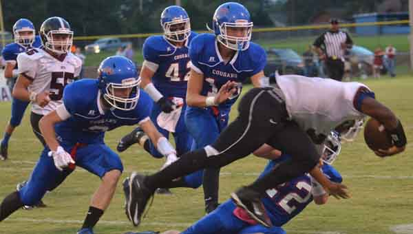 CONTRIBUTED PHOTO   MERICA TISDALE Nathan Scoggins (2), Colten Kelley (13) and Cole Roper (22) take down a South Montgomery player during last Friday's 26-6 beating.