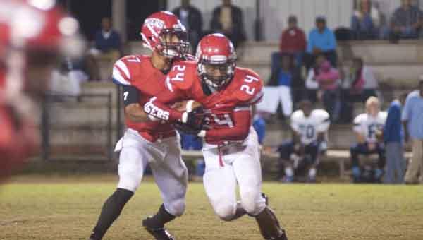 Quarterback Austin Bryant (7) hands off the ball to Tyrus Jones.