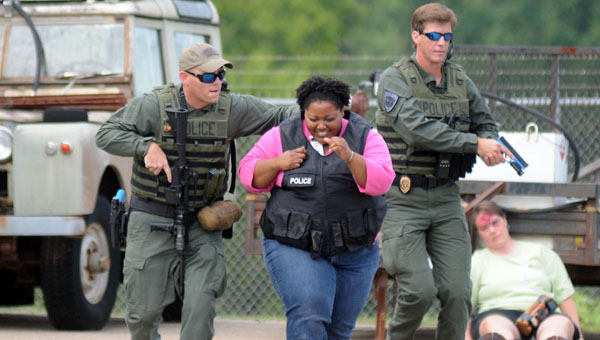 Sgt. Andy Beck, left, and Capt. Justin Lovvorn, right, of the Greenville Police Department Special Response Team, lead a hostage to safety during a full-scale exercise in August of 2014 at Mac Crenshaw Memorial Airport. The Greenville Police Department is offering a new self-defense course in the event of an active shooter situation. (File Photo)