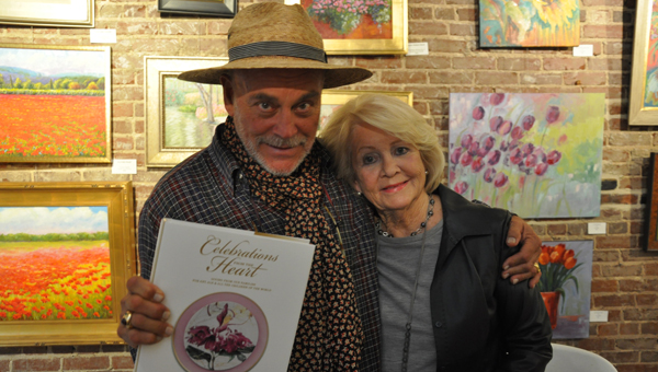 Alabama artist Nall Hollis held an exhibit Friday night at the High Horse Gallery.  Along with etchings and paintings by Hollis, the book Celebrations from the Heart: Giving From our Families for Art, ALS and All the Children of the World, which contains art by Hollis as well as the famous Sister Schubert recipes, could be purchased.  Pictured, left to right, Nall Hollis and Betty Sims. (Advocate Staff/Beth Hyatt)