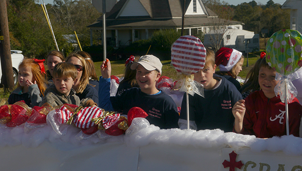Children from Grace Baptist toss candy from their church's float to parade-goers during the McKenzie parade. (Advocate Staff/Angie Long)