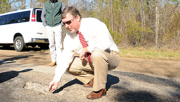 """Butler County Engineer Dennis McCall examines a portion of County Road 17. Many of the county's minor collectors are approaching """"complete failure"""" and will likely one day have to be returned to unpaved roadways. (Advocate Staff/Andy Brown)"""