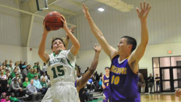 Brantley freshman Parker Driggers goes for a layup as the Blacksher Bulldogs close in. In a heated match between the Bulldogs, Blacksher proved victorious at 73-71with less than a second left in the game. (Photo by Beth Hyatt)