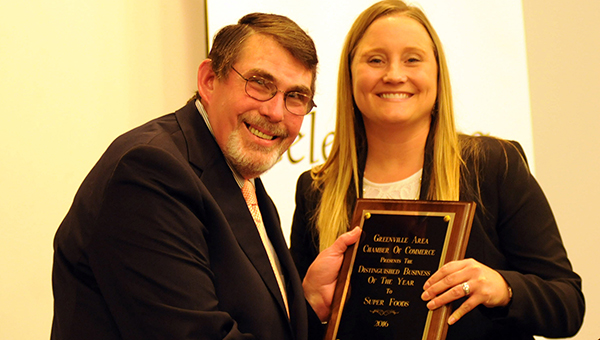 Tracy Salter, right, presents Super Foods owner John Wilson with the Distinguished Business of the Year award during Thursday night's Greenville Area Chamber of Commerce Banquet. (Advocate Staff/Andy Brown)