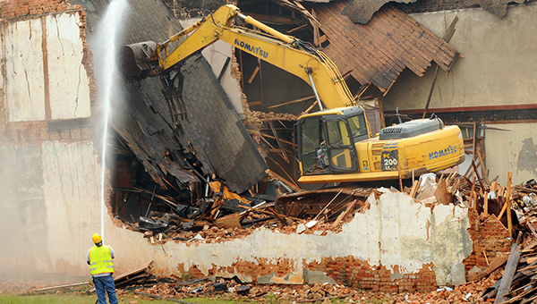 Workers demolished several crumbling structures along Commerce Street near the Greenville Area Chamber of Commerce on Wednesday to help clear the way for the creation of a veterans park. (Advocate Staff/Andy Brown)