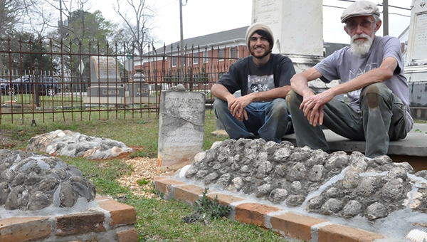 Matthew Iovino (left) and Ray Hall (right) in front of three of the graves they restored in Greenville's Pioneer Cemetery.  (Advocate Staff/Beth Hyatt)
