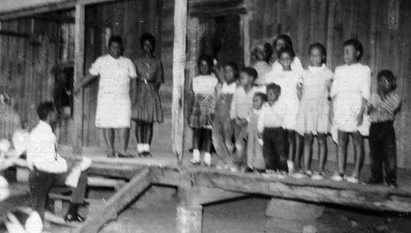 Wilbert and Rosia McGhee had 13 children. The children gathered for a photo on the porch of their family home, which was burned down shortly afterward.