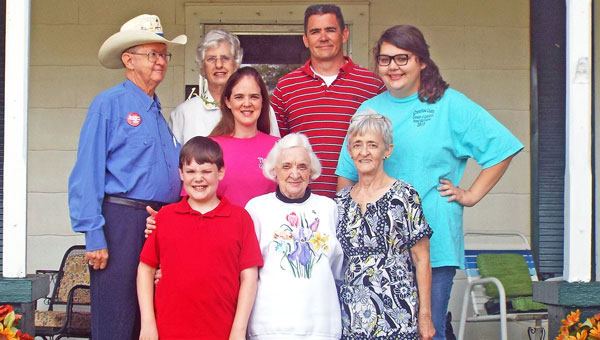 From left (top), Flynn Gregory, Ikey Gregory, Connie Lorraine Garmon, Kevin Christian and Alexis Lorraine Christian, and (bottom) Christian Garmon, Hazel Lorraine Flynn Gregory and Fran Lorraine Christian in front of the second home built on the family's land in 1921, current home to Hazel Gregory.